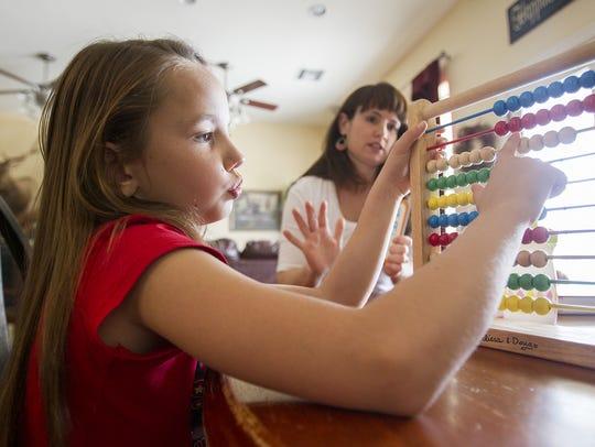 Gina Ray's three children work on school work in their