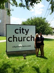Nathaniel and his wife Haley in front of the City Church sign. provided photo
