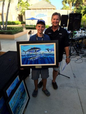 Hayden Hawes (left), top junior angler at last weekend's Mako Owners Funament at the Hutchinson Island Marriott Marina in Stuart, is presented with his award by host George Poveromo of 'George Poveromo's World of Saltwater Fishing' television show. (Contributed photo by George Poveromo)