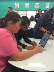 Danielle Lowe and Isaiah Rich, fifth-graders at South Knoxville Elementary, work a puzzle using the Osmo educational game system for iPad in the renovated library. Lowe and Rich are among the Student Council members who contributed ideas to the renovation.