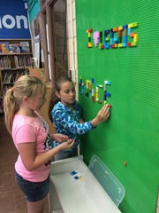 South Knoxville Elementary fifth-graders Kaylee Galyon, left, and Rory Daulton spell out their principal's name, Dr. Nicely, on the renovated school library's Lego wall. Both girls are members of Student Council.