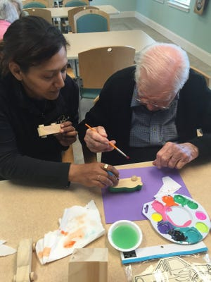 Contributed photo Lynda Berglund, an activity assistant at Mirador, helps a resident with art therapy.
