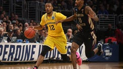 Michigan guard Muhammad-Ali Abdur-Rahkman drives against