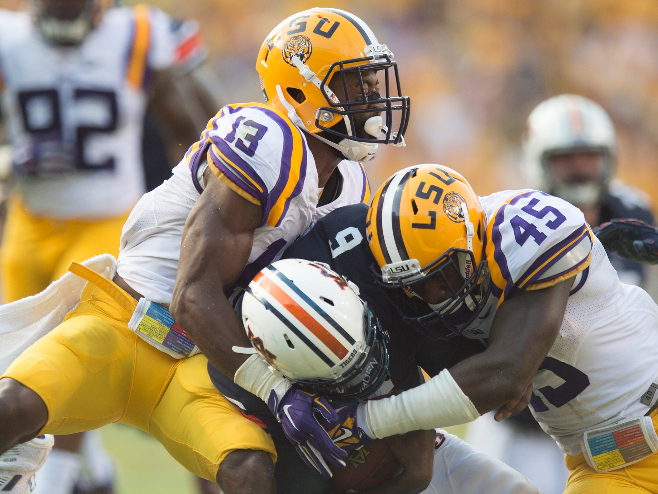 Louisiana State defensive back Dwayne Thomas (13) and Louisiana State linebacker Deion Jones (45) tackles Auburn Tigers quarterback Jeremy Johnson (6) during the NCAA football game between LSU Tigers and Auburn on Saturday, Sept. 19, 2015, at Tiger Stadium in Baton Rouge, La. LSU Tigers defeated Auburn Tigers 45-21.