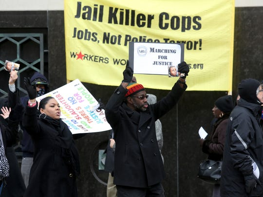 """The Detroit marchers carried signs and chanted """"No justice, no peace."""""""