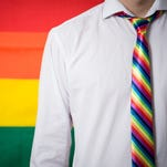 Man wearing shirt and rainbow tie