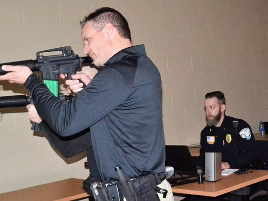 Oconto County Deputy Todd Skarban holds a mock rifle as he participates in firearms training last spring at the Sheriff's Office. Behind him seated is Oconto Falls Police Chief Brad Olsen, who coordinating the simulations for deputies being trained, with Chief Deputy Ed Janke observing.