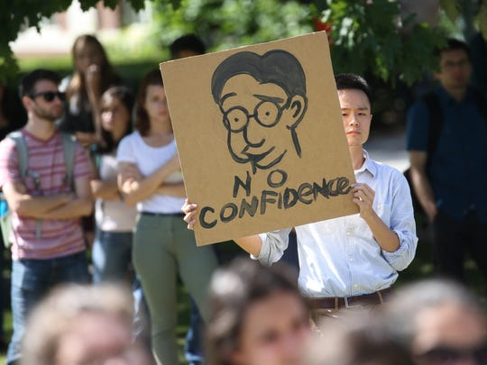 Harry Gu, a UR student, holds a poster with cartoon of Joel Seligman on it during a protest Wednesday over  dissatisfaction of UR's handling of sexual harassment allegations against professor.