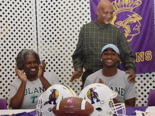 Judy Harris (left), mother of ASH football player Jorien Vallien, and Grandy Vallien, father of Jorien, congratulate their son after he signed to play football at Tulane University in New Orleans.