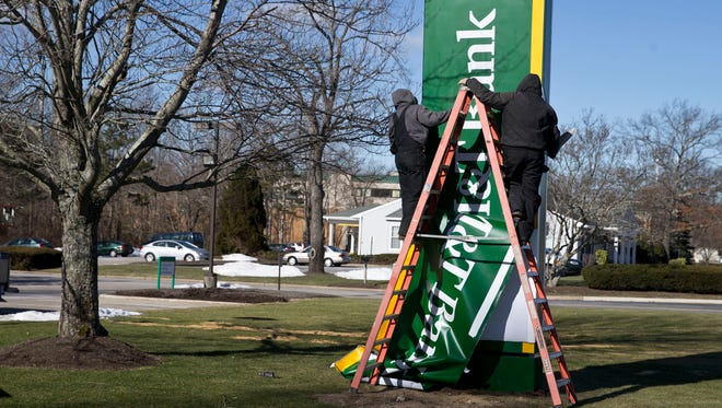 Chris Kennedy and Bill Walsh of NW Sign Industries, Moorestown, work on replacing the sign at the Toms River branch of Hudson City Savings Bank with its new owner, M&T Bank.