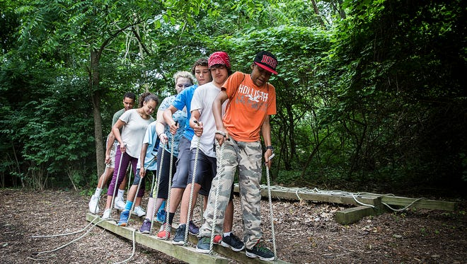 Boys and Girls Club members work together to walk two wooden beams in a circle at Camp Adventure during the Youth Leadership Boot Camp Tuesday morning.