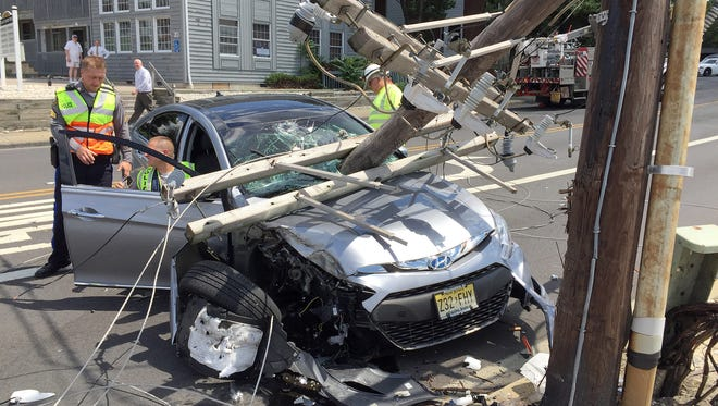 Toms River Police continue their investigation of a single car accident on East Water Street in the township, Wednesday, June 22, 2016.  The accident cut off power to many of the township and county buildings in the downtown area.