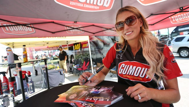 NHRA driver Leah Pritchett prepares to sign autographs for fans at Lucas Oil Raceway, Friday, September 4, 2015.