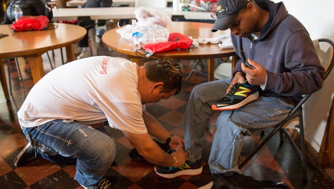 Anthony Weinert, an Oakland County foot surgeon, left, helps Dwight Carroll, an Army veteran, to fit a pair of new shoes, at the Emmanuel House, Friday, May 26, 2017, in Detroit.