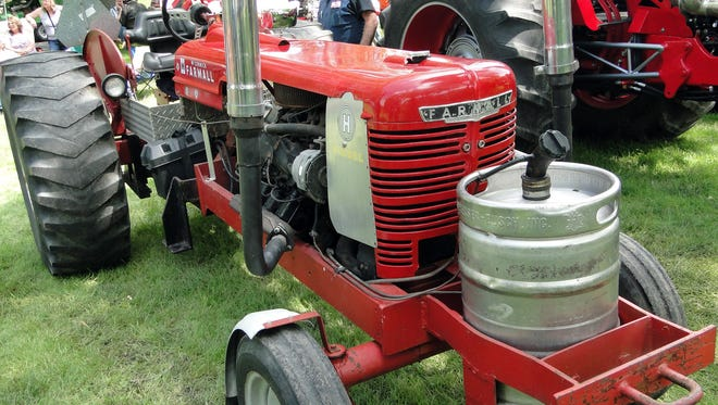 Bob Justman extended the body length of his IH tractor just to accommodate an automatic transmission, something he says makes it easier for driving in parades.  The Chevrolet engine in the tractor is fueled with diesel that is stored in the Budweiser beer keg mounted in the front of the tractor.