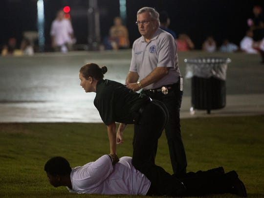 Chris Murphy, director of the Montgomery Department of Public Safety, and Lt. Christina Thornton assist in arresting a suspected after someone fired a shot while in a crowd just before the start of fireworks at Riverfront Park in Montgomery, Ala., on Saturday, July 18, 2015.
