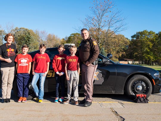 From left to right: Indian Woods Elementary School teacher Maureen Maki, fifth-graders Kenny Thomas, 10, Riley Thompson, 10, Laura Hannan, 10, Nick gorinac, 10, and St. Clair County Deputy Damon Duva. The Indian Woods Student Council raised money to buy fleece and made blankets that are being donated to the St. Clair County Sheriff's Department to give to children in emergencies.