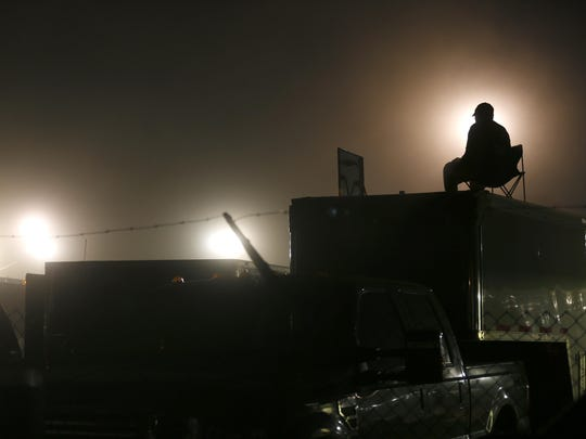 A spectator watches the races on top of a team trailer on a recent Saturday night.