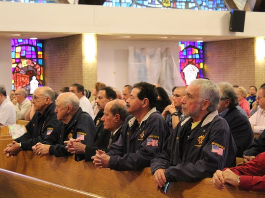 Members of the Pallotti Council of the Knights of Columbus kneel during the Blue Mass, which was attended by dozens of people.