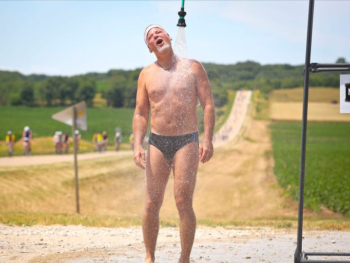 Rick Faugle of Urbandale on Team Sprint and his 14th ride, takes a hose shower break courtesy of Donna and Jason Meyer of rural Yale Monday July 22, 2013 on the way  Perry during RAGBRAI XLI.