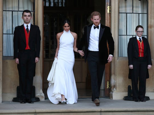 Meghan Markle, now the Duchess of Sussex, leaves a Windsor Castle reception with husband Prince Harry after she changed into a white halter-top dress from designer Stella McCartney.