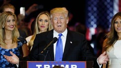 Donald Trump stands with his family while discussing