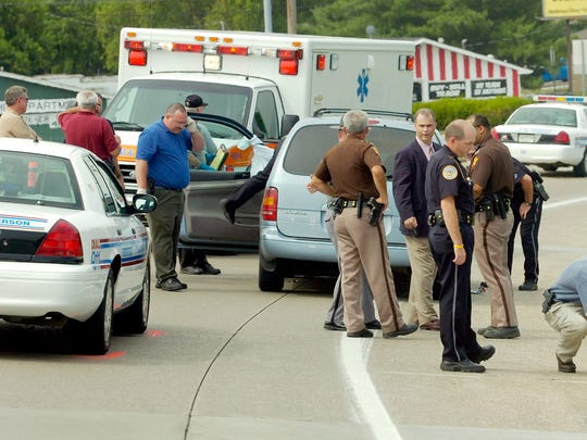 Henderson and Evansville Police officers on the scene at the U.S. 41-U.S. 60 cloverleaf where two suspected bank robbers shot and killed themselves Friday morning after a pursuit that began in Evansville. (Gleaner photo by Mike Lawrence ¥ 831-8346 or mlawrence@thegleaner.com) 07/01/2005