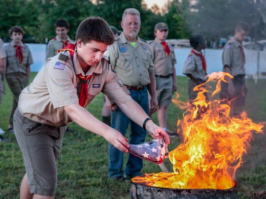 Danny Farone of Troop 538 retires an American flag during Saturday evening's portion of the Healing Field events.