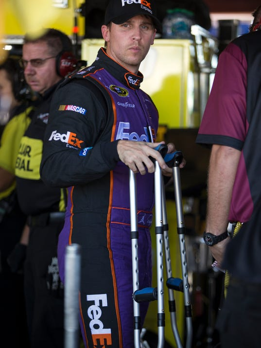 Denny Hamlin talks with his mechanics during practice for the NASCAR Sprint Cup auto race at Richmond International Raceway in Richmond, Va., Friday, Sept. 11, 2015. Hamlin, who tore an ACL, will be racing despite his injury. (AP Photo/Chet Strange)