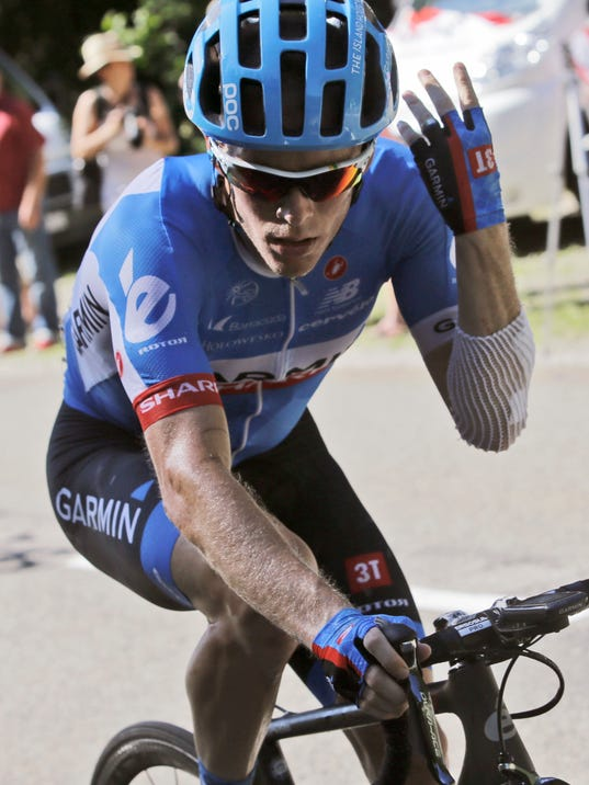 Andrew Talansky of the U.S. strains as he rides alone with more than 20 minutes delay on the pack because of back pain during the eleventh stage of the Tour de France cycling race over 187.5 kilometers (116.5 miles) with start in Besancon and finish in Oyonnax, France, Wednesday, July 16, 2014. Talansky crashed twice in the first week of the Tour. (AP Photo/Laurent Cipriani)