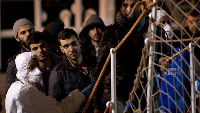 Migrants wait to disembark in the Sicilian harbor of Pozzallo, Italy, early Monday.