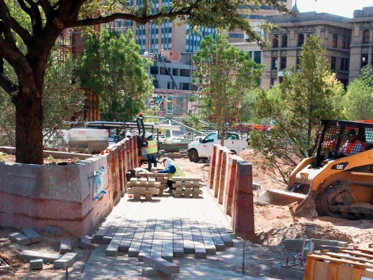 Workers install paving stones Tuesday on the Northwest corner of San Jacinto Plaza. Read about other city council action on page b1.
