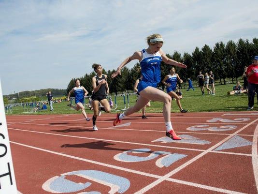 Lower Dauphin's Joely Helder wins the 100 meter dash ahead of Palmyra's Camryn Simpson.