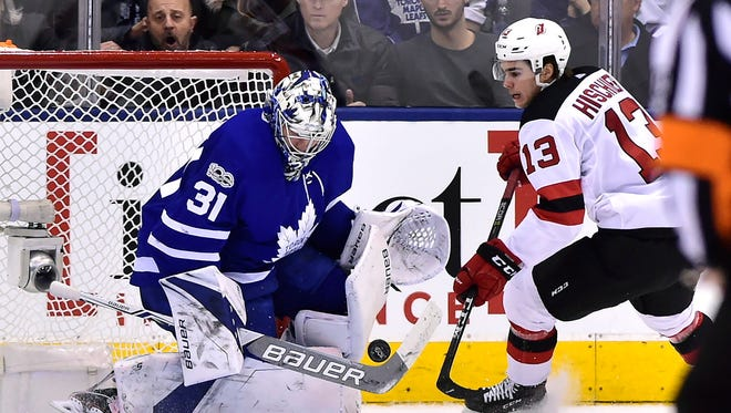 Toronto Maple Leafs goalie Frederik Andersen (31) makes a save on New Jersey Devils center Nico Hischier (13) during the second period of an NHL hockey game Thursday, Nov. 16, 2017, in Toronto.