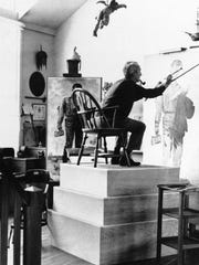Norman Rockwell wields his brushes from a platform