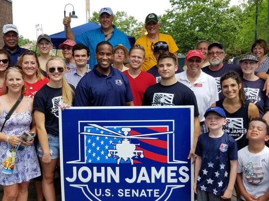 Supporters of John James, center, a Republican candidate for the U.S.Senate, at a grill-out in Traverse City on June 30, 2018.