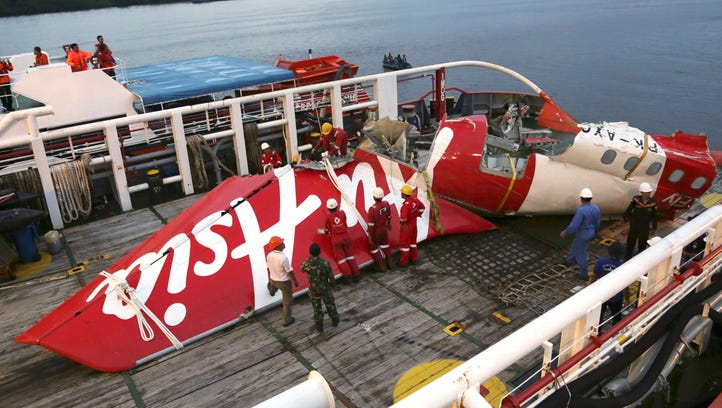 Workers prepare to unload the newly-recovered tail