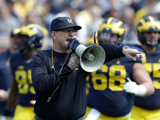 FILE - In this April 15, 2017, file photo, Michigan head coach Jim Harbaugh talks to his players during the NCAA college football team's spring game, in Ann Arbor, Mich. The increasing visibility of spring football games has offered plenty of feel-good moments and fan-friendly opportunities. What they don't provide is much insight into what these teams will be doing this fall. With so many spring games on television, teams don't want to give anything away to rival coaches who may be tuning in. (AP Photo/Carlos Osorio, File)