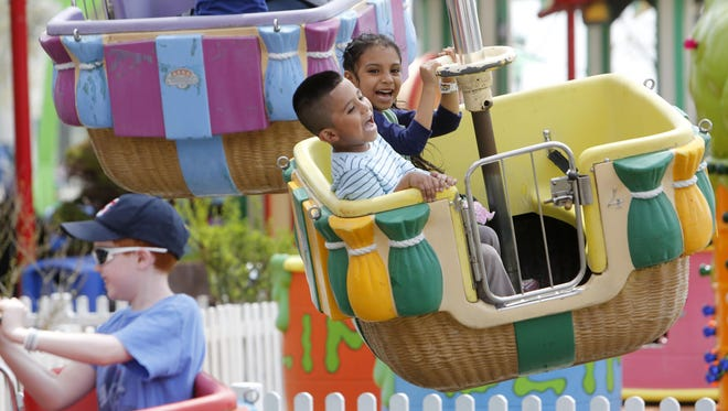 Children ride the Up, Up and Away ride at Playland in May 2014.