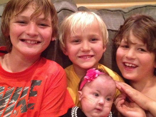 Hope Harrison shares a cuddly moment with her three brothers, from left, Cooper, Tucker and Hudson.