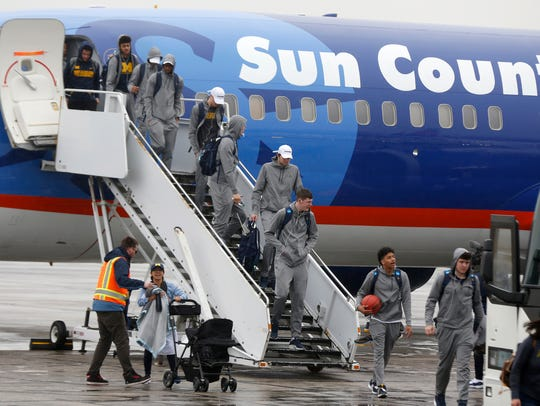 The Michigan basketball team exits its plane at Willow