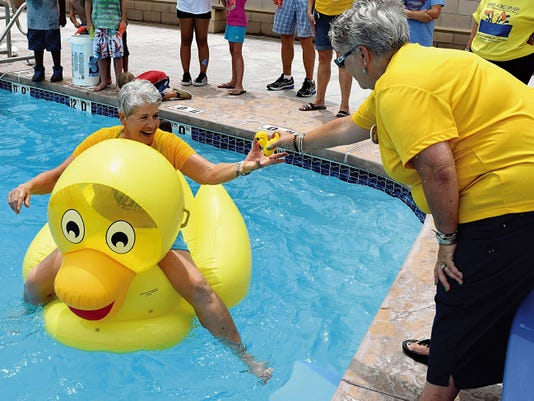 Donna Hill passes a rubber duck to Debra Killgore midway through a race Saturday at the Elks Lodge.