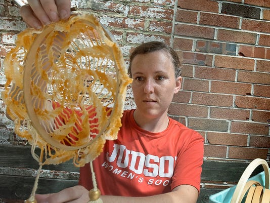 """Christina Carter of York City demonstrates how to make a do-it-yourself dream catcher in the courtyard at Cherie Anne Designs Monday, Aug. 31, 2015. She is a friend of Revolt Style Studio owner Jessica Weikert who is hosting a pop-up shop in the courtyard during Boutique Week which runs Sept. 1-5. During Thursday's """"Makers Night"""" Jessica will be on hand to to guide participants in making the dream catchers using found and vintage items. Participating retailers will extend store hours until 7pm and offer in-store promotions, activities and trunk shows. The event is sponsored by Members 1st Federal Credit Union. Bill Kalina - bkalina@yorkdispatch.com"""