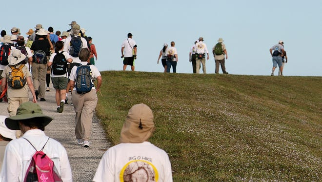Hikers ascend the levee and begin their trek around Lake Okeechobee. Hikers ascend the levee and begin their 8-mile trek around Lake Okeechobee.