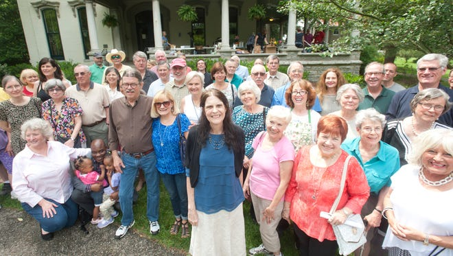 Neighborhood activists, beautification advocates, historic preservationists and friends stand behind The Courier-Journal writer Martha Elson (center, black sweater) at the Peterson-Dumesnil House to honor Elson's reportorial service to their communities. 20 May 2017