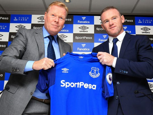England soccer star  Wayne Rooney, right, holds an Everton shirt  with his new manager Ronald Koeman during the press conference at Goodison Park, Liverpool, England Monday July 10, 2017. Rooney returned to his original club Everton from Manchester United.  (Nigel French/PA via AP)