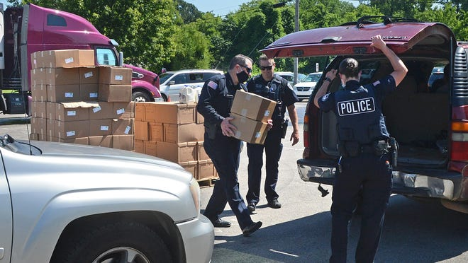 Fort Smith Police Chief Danny Baker, from left, with officers Ryan Arritt and Robyn Shoptaw help to load food items into vehicles on Friday, June 5, 2020, during an Antioch for Youth and Family Drop and Go. Charolette Tidwell, founder and director of Antioch, said more than 2,600 individuals were served during the food giveaway.