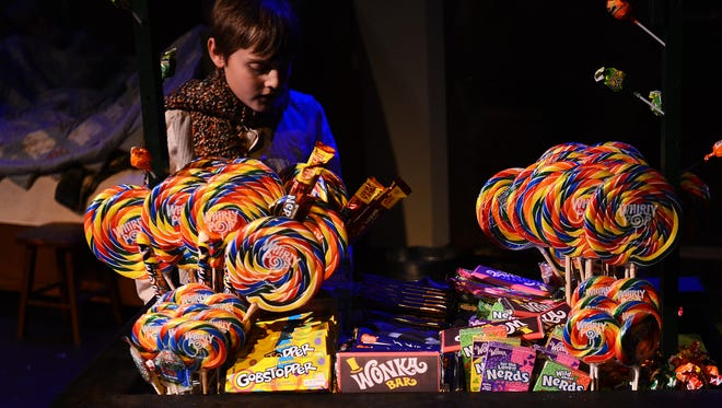 Character Charlie Bucket, played by 11-year-old Brian Martin, buys a Wonka candy bar, during a dress rehearsal Wednesday night