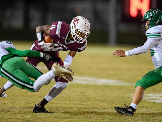 Henderson's Isaac Anglin (4) slips a tackle from Meade's