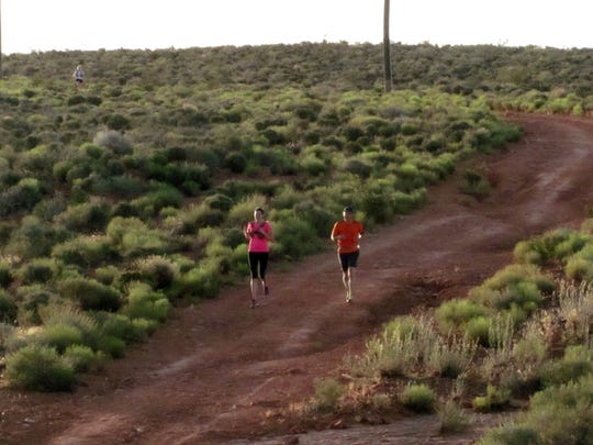 Karen Funk and Tony Ort participate in a group trail run on the Prospector Trail in the Red Cliffs Desert Reserve on Wednesday, May 27, 2015.